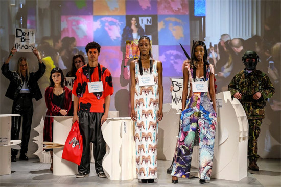 """Vin + Omi apresentam o projeto Bin2Body no começo da Semana de Moda Masculina de Londres. Na extrema esquerda, a placa """"Don't be trashy""""!"""